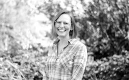 Black and white image of Bree Norlander smiling in front of Summer foliage