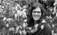 A black and white photo of Stacey standing and smiling in a leafy area. She is wearing a patterned scarf, a dark cardigan, and a dress.