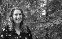 A black and white photo of Claire standing in front of leafy trees.