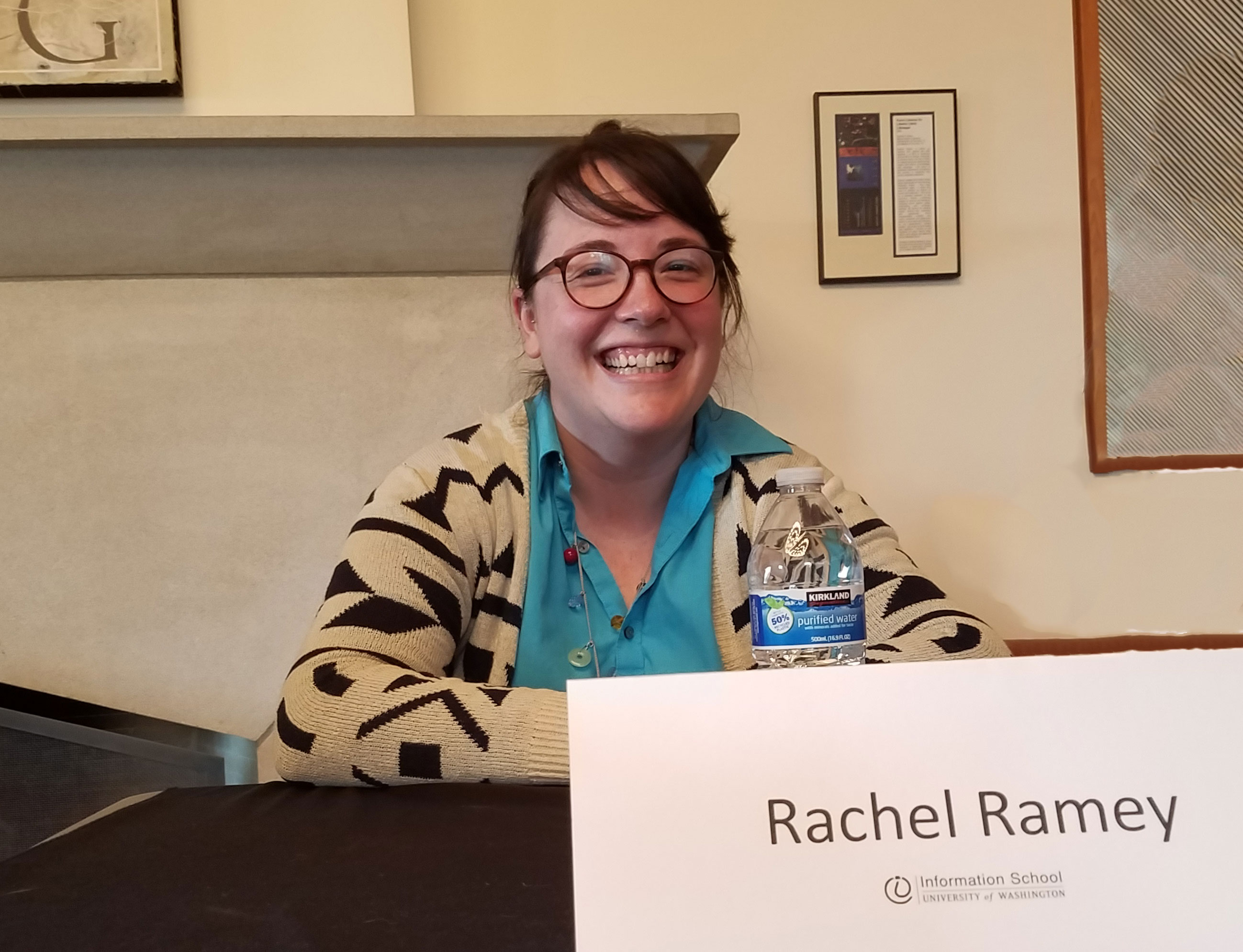 Smiling, young woman wearing glasses seated at a table with a name tag that reads Rachel Ramey.