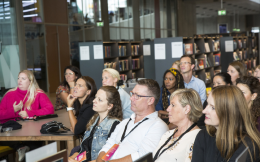 A group of people sitting in front of bookshelves in a library. They are looking up and listening to a presentation, though neither the presentation nor the presenter are visible in the image.