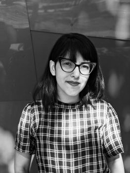 A black and white photo of Itza. She has dark hair with bangs and is wearing glasses and a checkered shirt.