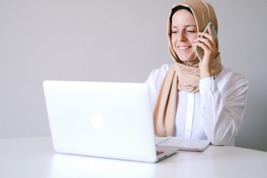 A woman sitting in front of her computer and talking on her mobile phone. She is wearing a white button up shirt and a tan headscarf.