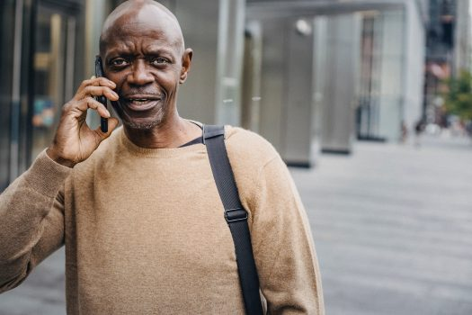 A man wearing a tan sweater talking on his cell phone outside.