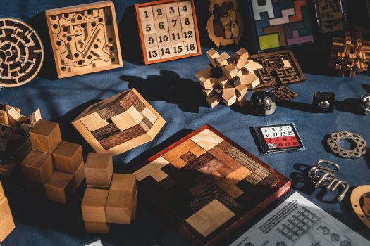 Several wooden puzzles and toys sitting on top of a piece of dark blue cloth.